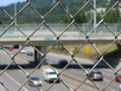 Looking down at a freeway through a chain link fence
