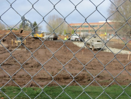 Cement trucks through a chain link fence