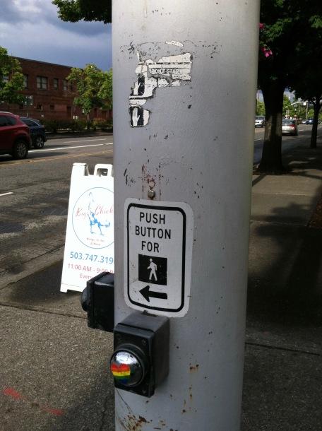 Crosswalk button with a pride heart sticker on it