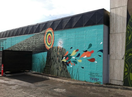 Mural of a tree stump and leaning log with multicolor rings in the cross section