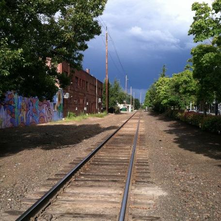 Railroad tracks going under storm sky,