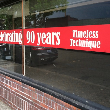 Banner on closed shop window saying Celebrating 90 Years Timeless Technique