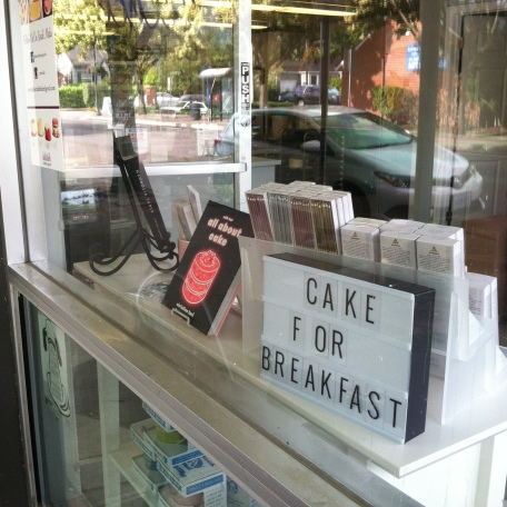 shop window with sign saying cake for breakfast