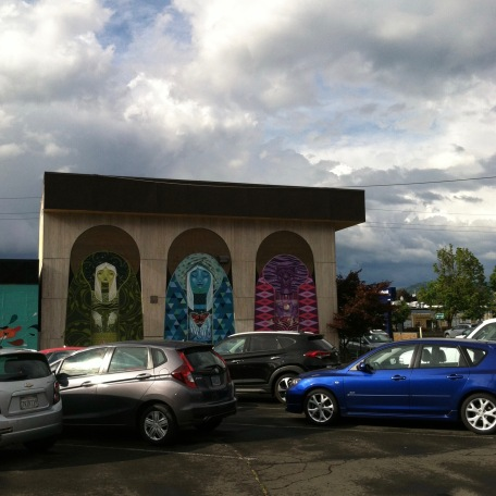 Mural of three female faces with cars parked in front