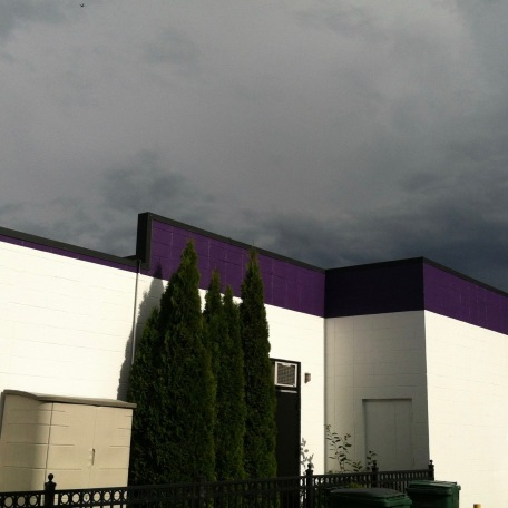 Purple and white building with storm sky.