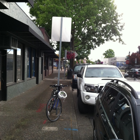 Bike parked on a pole, with auto dealer in the distance.