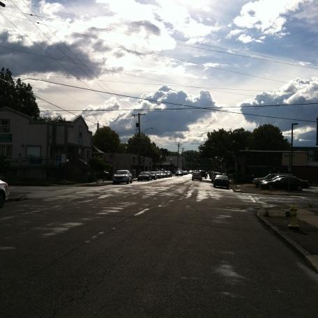 Street under clouds, with sun glare
