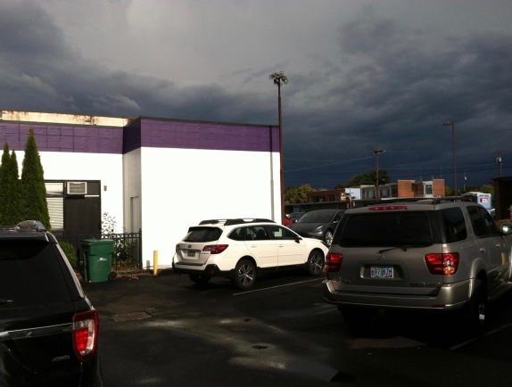 Very dark blue sky with a white & purple building in the foreground