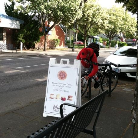 person locking up their bike on the sidewalk