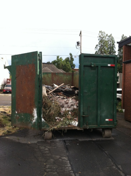 An extra large dumpster with bricks & rubble in it