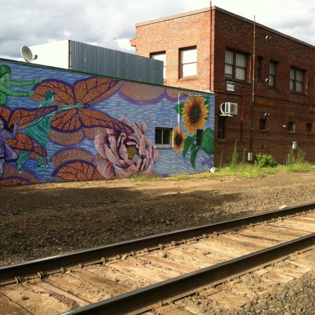 Mural and brick building next to railroad tracks.