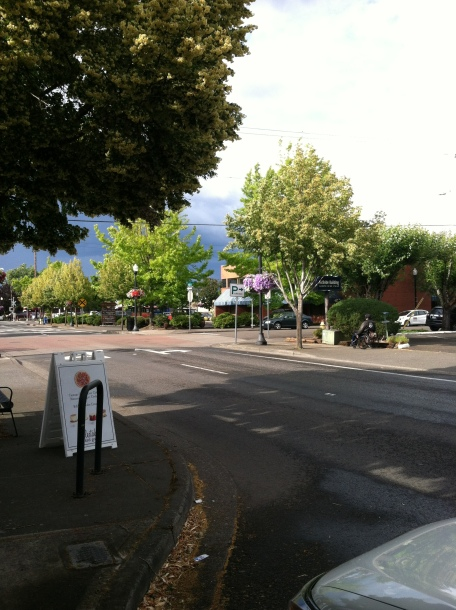 street scene, with person rolling down the sidewalk in their chair