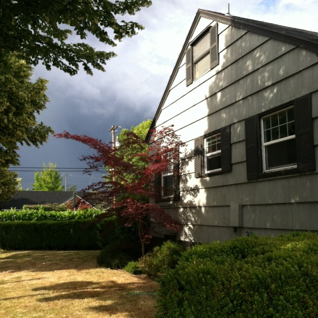 Side of house with clear blue sky on one side, dark storm clouds on the other