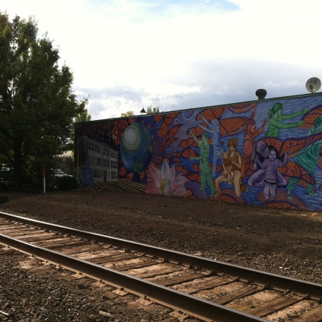 Railroad tracks and mural with butterflies and women on it.