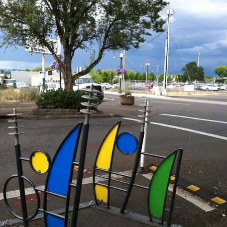 Bike parking that doesn't work, but it's blue green & yellow panels are pretty under the storm sky.