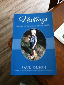 Blue book cover, with the title in white type, Nestlings, with photo of a boy barefoot in the grass, and the words, Paul Olson.