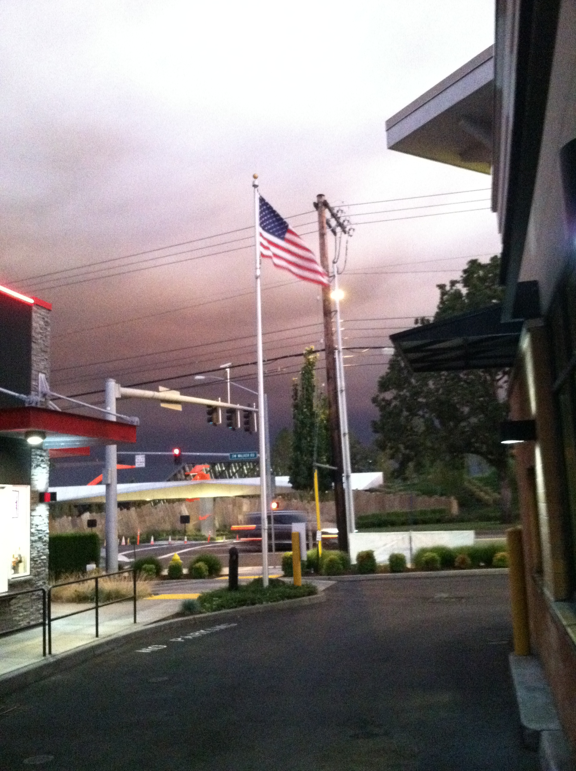 A reg white and blue flag waving in a coffee drive through in front of purple brown skies over a traffic light and Nike entrance with orange Nike logo